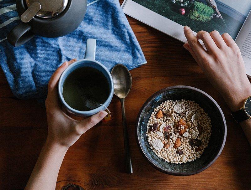Aamiainen kulhossa ja kupillinen teetä