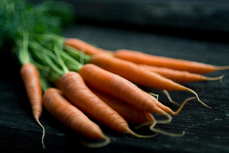 Porkkanoita mustalla puupöydällä