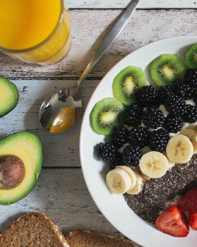 Vitamiinipitoisia hedelmiä lautasella ja lasillinen appelsiinimehua