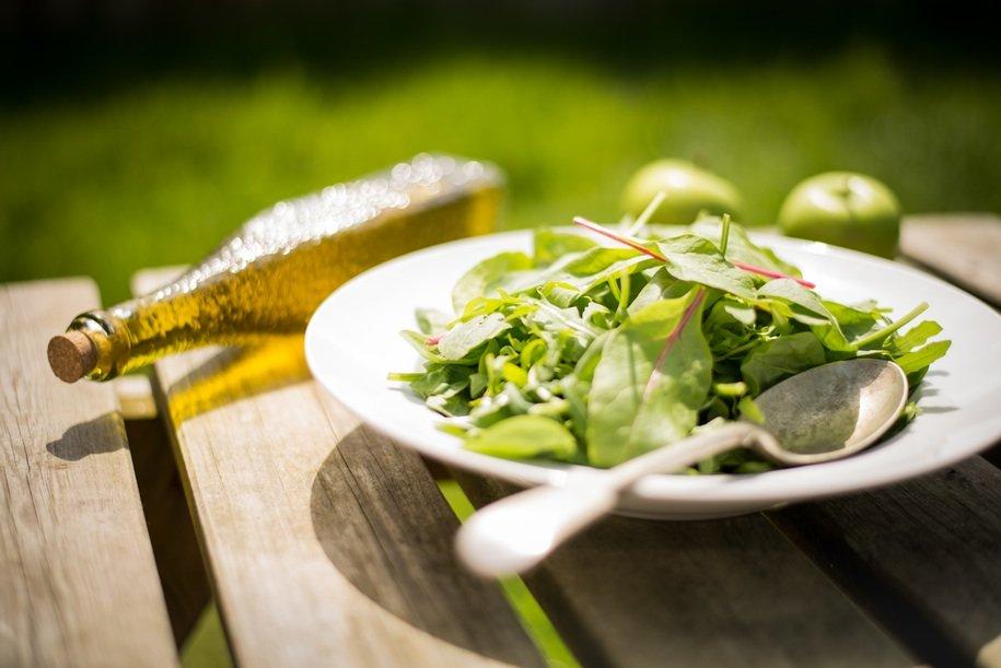 Salaattia lautasella, öljypullo ja kaksi omenaa